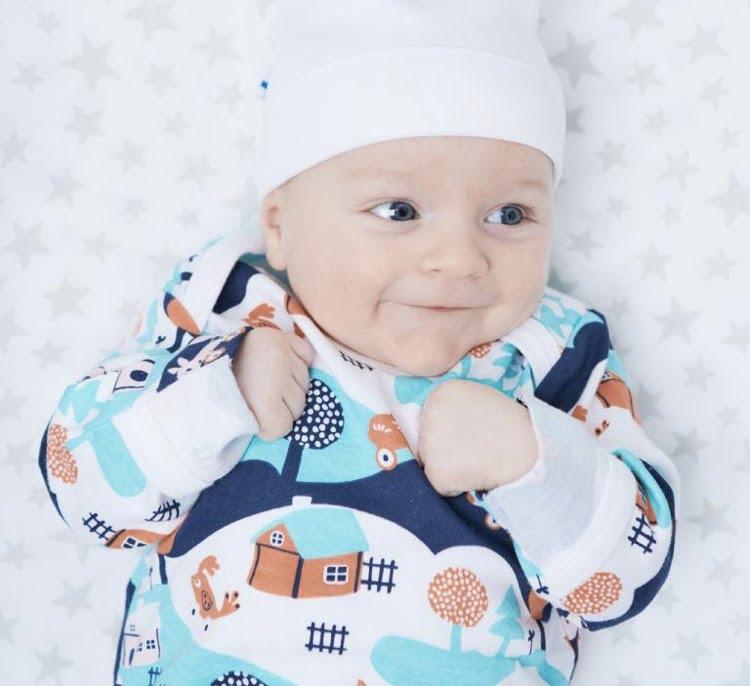 フィンランド・ベイビー・ボックスのオリジナル版を着て微笑む赤ちゃん